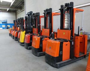 row of forklifts in warehouse